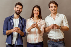 Group of young people. Group of attractive young people holding a smartphone, looking at camera, smiling, on a gray background Royalty Free Stock Photography