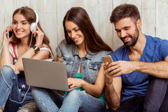 Group of young people. Group of attractive young people sitting on the floor using a laptop, Tablet PC, smart phones, headphones listening to music, smiling Stock Image
