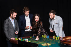 Group of young people behind roulette table Stock Image