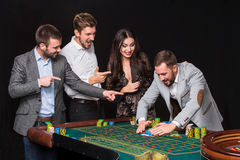 Group of young people behind roulette table Royalty Free Stock Photo