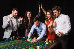 Group of young people behind roulette table on black background Royalty Free Stock Photography