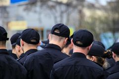 A group of young people in black uniform is standing on a city street. Uniformed police officers, boys and girls, maintain order royalty free stock image