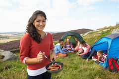 Group Of Young People On Camping Trip In Countryside. Cooking food stock photos
