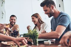 Good times. Group of young people in casual clothing eating and smiling while having a dinner party indoors stock photography