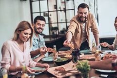 So tasty. Group of young people in casual clothing picking pizza and smiling while having a dinner party indoors stock photo