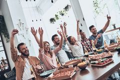 Playful friends. Group of young people in casual wear gesturing and smiling while having a dinner party stock photos