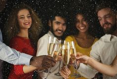 Group of young people celebrating new year with champagne at night club. Christmas party time. Young people toasting with champagne flutes. Multiethnic friends Royalty Free Stock Image