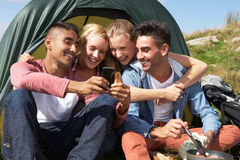 Group Of Young People Checking Mobile Phone On Camping Trip. Laughing Stock Images