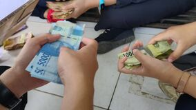 A group of young people are counting money at outdoor