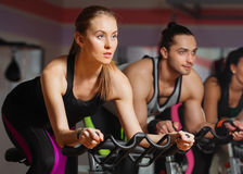 Group of young people cycling in class in gym Stock Photos