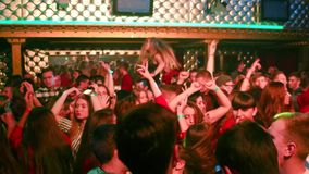 Group of young people dancing at the event in a nightclub girl waves her hands on his shoulders stock video