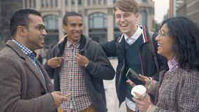 A group of young people of different nationalities cheerfully communicate and laugh at the background of the busy street. Of the big city.Berlin circa stock footage