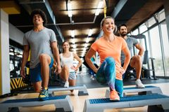Group of young people doing exercises in gym royalty free stock photo