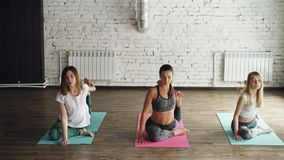 Group of young people are doing yoga exercises moving from King Pigeon pose to Eka Pada Rajakapotasana. Women are. Concentrated on maintaining position. Studio stock footage