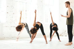 Group of young people doing yoga in gym stock image