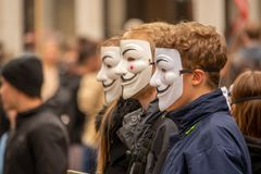 group of young people dressed all in black goes out on the street to demonstrate with anonymous masks stock photo