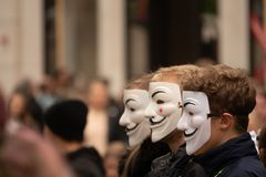 Group of young people dressed all in black goes out on the street to demonstrate with anonymous masks stock photos