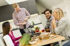 Group of young people drinking wine in the room royalty free stock photography