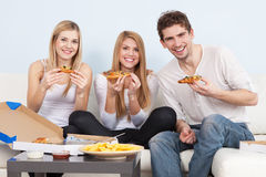 Group of young people eating pizza at home Stock Photo