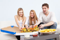 Group of young people eating pizza at home Royalty Free Stock Image