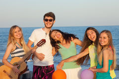 Group of young people enjoying beach party with playing guitar a Stock Image