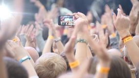 Group Of Young People Enjoying Outdoor Music Festival. Close-up rear view of crowd on concert. Funny people shoot a royalty free stock images
