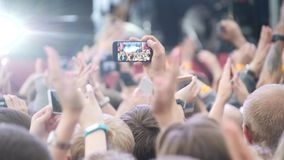 Group Of Young People Enjoying Outdoor Music Festival. Close-up rear view of crowd on concert. Funny people shoot a
