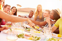 Group Of Young People Enjoying Outdoor Summer Meal Stock Image