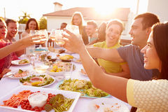 Group Of Young People Enjoying Outdoor Summer Meal Royalty Free Stock Photography