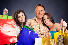 Group Of Young People Enjoying Their Shopping Spree. Studio shot of three young people enjoying a sale event Royalty Free Stock Images