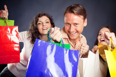 Group Of Young People Enjoying Their Shopping Spree. Studio shot of three young people enjoying a sale event Stock Image