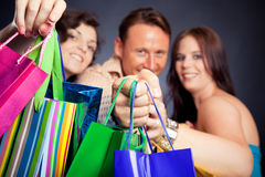Group Of Young People Enjoying Their Shopping Spree. Studio shot of three young people enjoying a sale event. focus on the bags in the forground Stock Photos