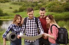 Group of young people exploring map in wilderness. Camping season stock photos