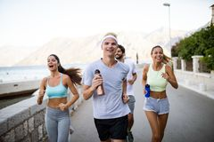 Group of young people friends running outdoors at seaside. Group of happy young people friends running outdoors at seaside royalty free stock photo