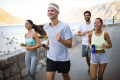 Group of young people friends running outdoors at seaside. Group of happy young people friends running outdoors at seaside royalty free stock photography