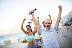 Group of young people friends running outdoors at seaside. Group of happy young people friends running outdoors at seaside royalty free stock image