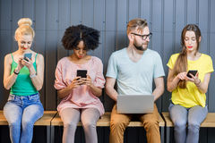 Group of young people with gadgets indoors Royalty Free Stock Photography