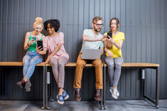Group of young people with gadgets indoors Royalty Free Stock Photo