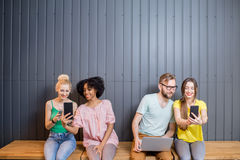 Group of young people with gadgets indoors Royalty Free Stock Photos