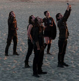 Group of young people in goth clothing looking up. Group of young people on the beach in late afternoon all dressed in goth clothing looking up.  One of them Royalty Free Stock Image