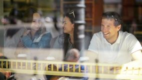 Group of Young People Having a Good Time at a Cafe and Waiting for Some Beverages. Two Women and One Man in Restaurant. Seen Through Window on the Street, HD stock video