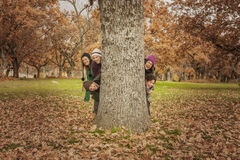 Group of young people hidden behind a tree. Autumn landscape Royalty Free Stock Photo