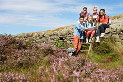 Group Of Young People Hiking Through Countryside Stock Photography