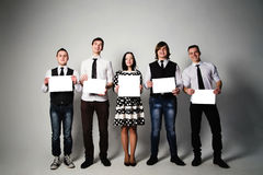 Group of young people holding sheets of paper Royalty Free Stock Image