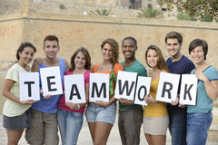 Group of young people holding teamwork sign Stock Photos