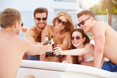 Group Of Young People On Holiday Relaxing By Swimming Pool. Holding Bottle Of Beer Making A Toast stock images