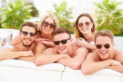Group Of Young People On Holiday Relaxing By Swimming Pool. Wearing Sunglasses Smiling stock photo