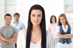 Group of young people indoors. Indoor portrait of group of smiling young people, attractive women in front looking at camera, smiling Royalty Free Stock Photos