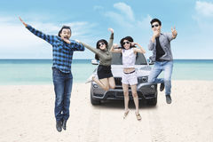 Group of young people jumping on beach. Multiracial group of young people wearing sunglasses, jumping together on the beach Royalty Free Stock Photography