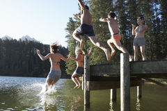 Group Of Young People Jumping From Jetty Into Lake Stock Photo